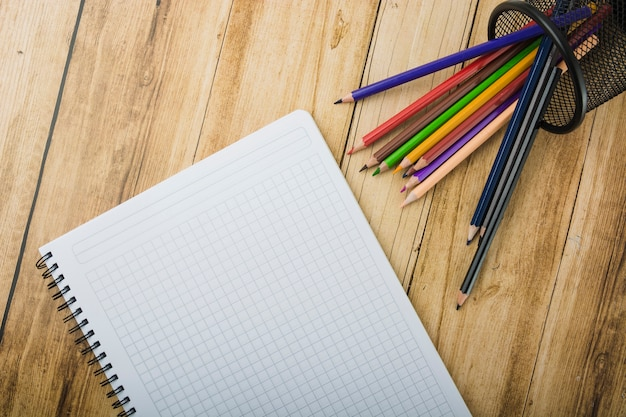Elevated view of notepad and colorful pencils on wooden background