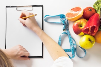Elevated view of a dietician's hand writing on clipboard with pencil