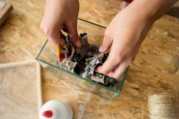 ガラス製の容器に裂けた紙を入れた女性の手の高さのビュー
