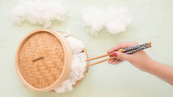Elevated view of a hand holding cotton with chopsticks from wicker steamer