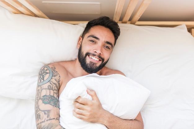 枕でベッドに横たわっている幸せな人の眺め