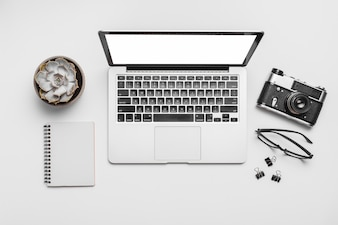 Elevated view of a laptop and retro camera isolated on white background