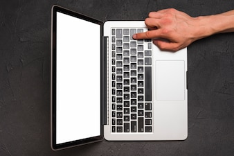 Elevated view of a person's hand using laptop on black background
