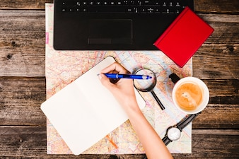 Elevated view of a traveler writing on blank notepad