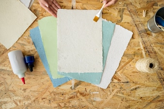 Elevated view of a woman's hand using paintbrush over handmade papers