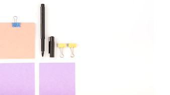 Elevated view of adhesive notes; pen and bulldog clips on white background