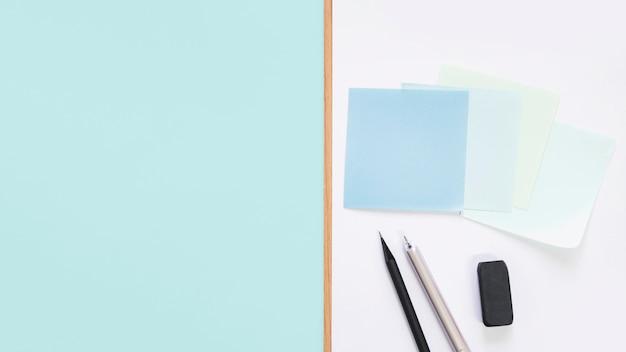 접착 메모의 높은 뷰; 펜; 책상에 연필과 지우개