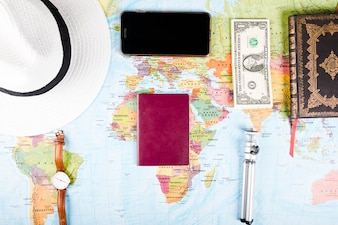 Elevated view of banknotes, smartphone and accessories on world map