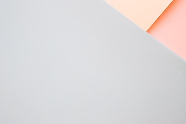 Повышенный вид бежевых и оранжевых картонных бумаг на углу серого фона