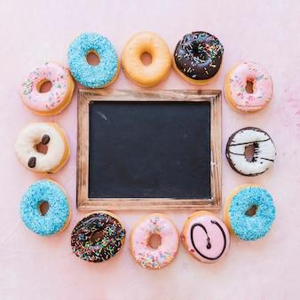 다양한 도넛으로 둘러싸인 빈 검은 슬레이트의 높은보기