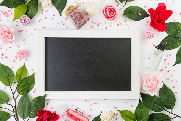 Повышенный вид пустой рамки в окружении косметических продуктов и листьев на белой поверхности