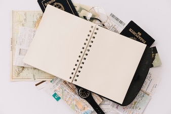 Elevated view of blank spiral notebook on passports and maps against white background