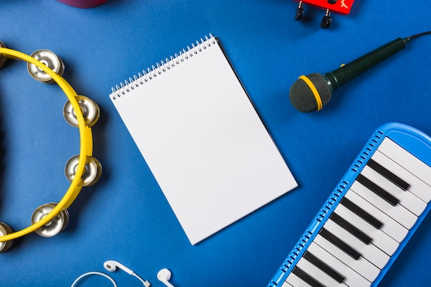 Повышенный вид пустого спирального блокнота с наушником; гитара; микрофон; фортепианная клавиатура и бубен на синем фоне