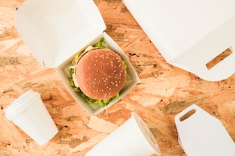 Elevated view of burger with disposal cups and packages on wooden background