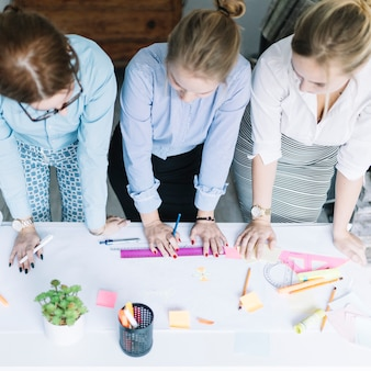 Elevated view of businesswomen planning the business chart on paper over desk