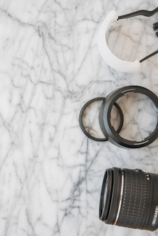 Elevated view of camera lens and accessories on marble textured background