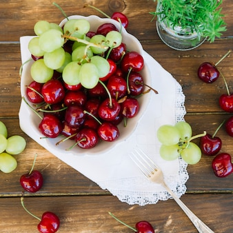 Elevated view of cherries and grapes in bowl on wooden plank