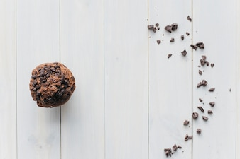 Elevated view of choco chip cupcake and scattered chocolate on wooden background