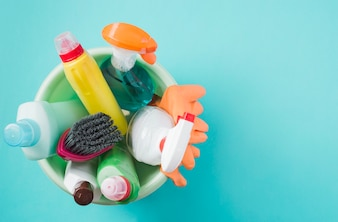 Elevated view of cleaning products in bucket in turquoise background