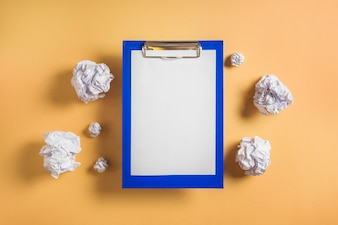 Elevated view of clipboard with blank paper surrounded by crumpled papers