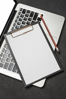 Elevated view of clipboard with blank white paper and pencil on laptop keypad