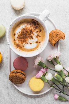 Elevated view of coffee and macaroons with bunch of fresh flowers