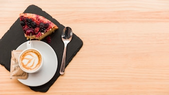 Elevated view of coffee latte and pastry on wooden table