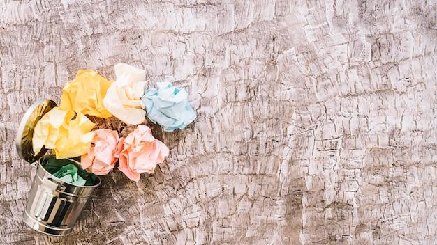 나무 배경에 쓰레기통에 다채로운 구겨진 종이의 높은 볼
