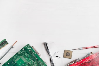 Elevated view of computer circuit boards and chip with tools on wooden background