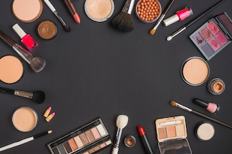 Elevated view of cosmetic products forming circular frame on black background