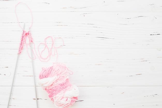 나무 배경에 분홍색 원사와 크로 셰 뜨개질의 높은보기