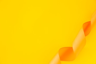 Elevated view of curled satin ribbon on yellow background