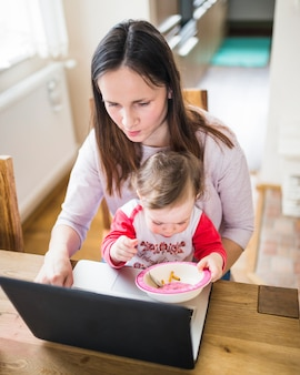 かわいい赤ちゃんの女の子は、彼女の母親がラップトップを使用して食べて食べる
