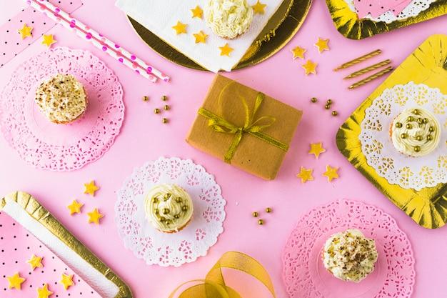 カップケーキと誕生日の贈り物と装飾的なピンクの背景の高さのビュー