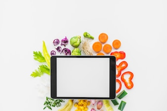 Elevated view of digital tablet and chopped vegetables on white background