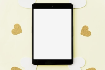 Elevated view of digital tablet surrounded with heart sticker on yellow backdrop