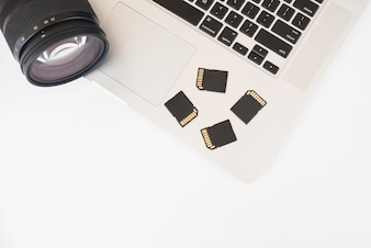 Elevated view of dslr camera and memory cards on laptop keyboard
