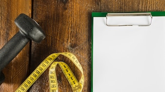 Elevated view of dumbbell; measuring tape and blank paper with clipboard