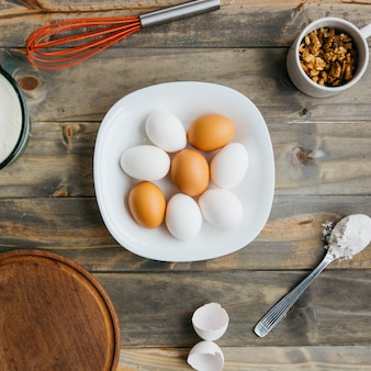 Elevated view of eggs; flour and walnut with whisk on wooden background