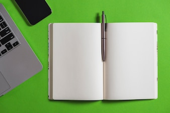 Elevated view of electronic gadget, notebook and pen on green background