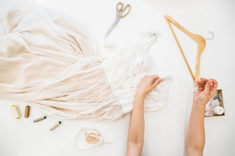 Elevated view of fashion designer's hand sewing dress over workdesk