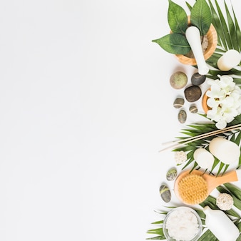 Elevated view of flowers; spa stones; leaves; brush and candles on white background