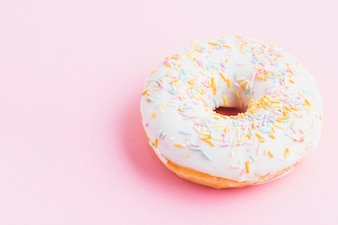 Elevated view of fresh decorative donut on pink background