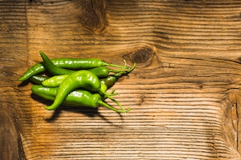 Elevated view of fresh green chili peppers on wooden surface