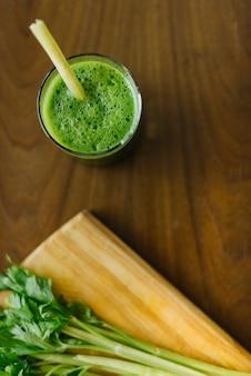 Повышенный вид свежий зеленый коктейль на деревянный стол