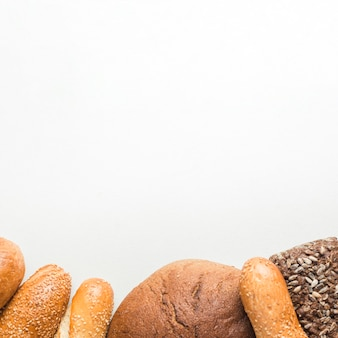 Elevated view of freshly baked breads at the bottom of white background