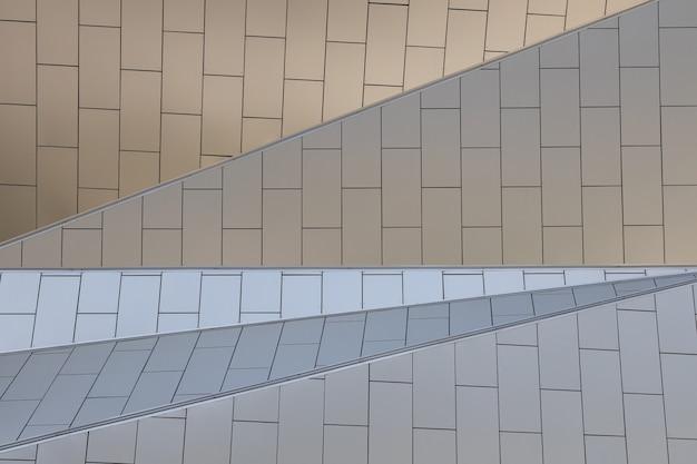 Повышенный вид геометрически спроектированного здания с белыми плиточными стенами