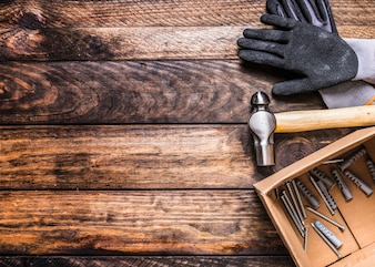 Elevated view of gloves, hammer, nails and wall plugs on wooden background
