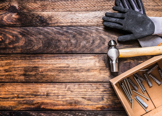 Повышенный вид на перчатки, молоток, гвозди и настенные розетки на деревянном фоне