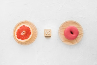 Elevated view of grapefruit versus donut on white background